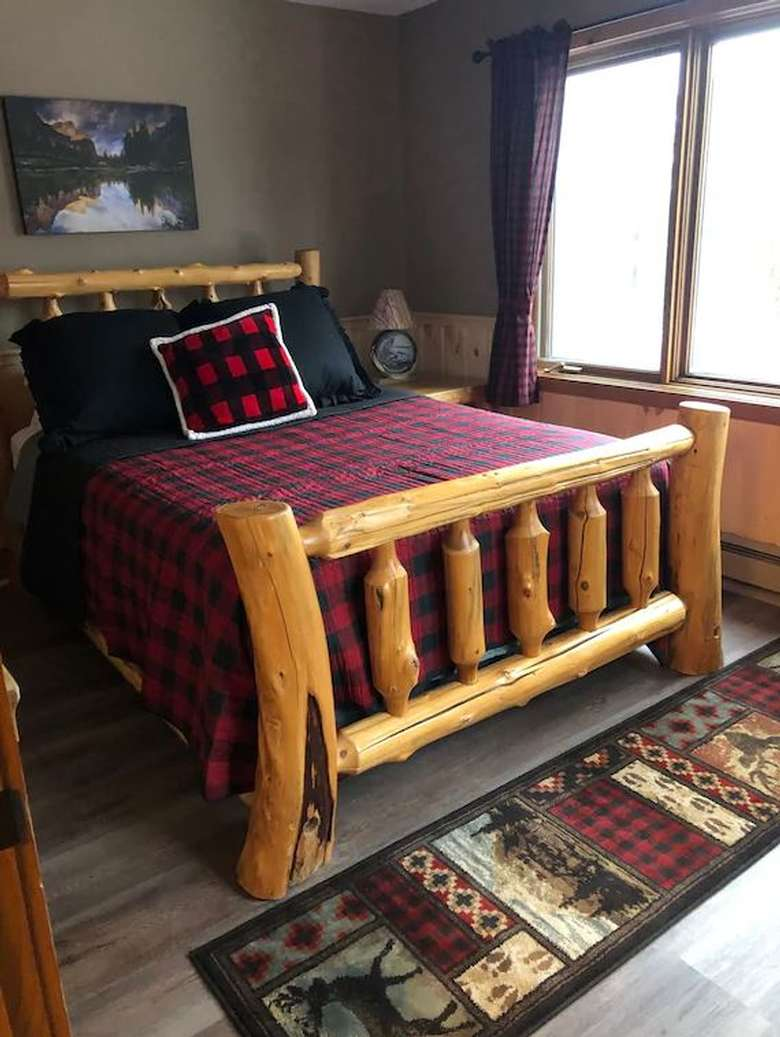 a bed with a log frame and red and black blanket