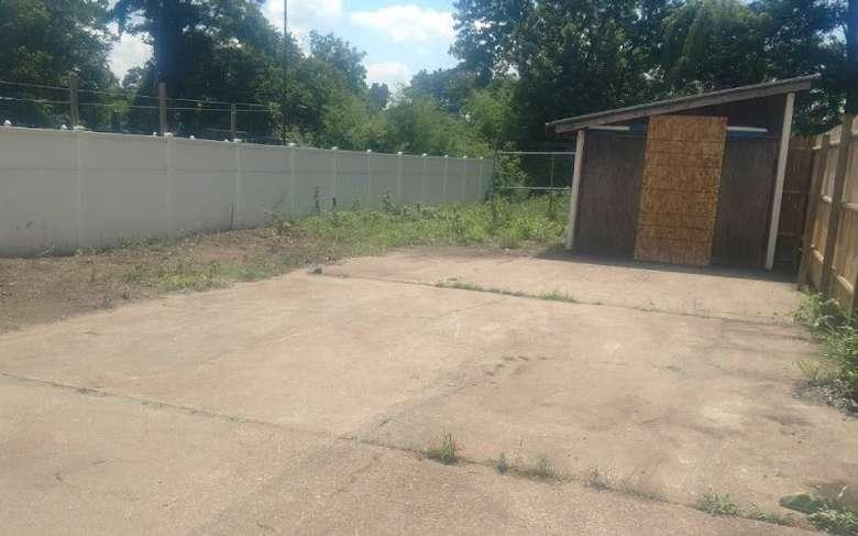 concrete area near a shed and fences
