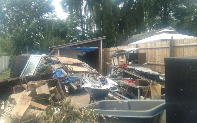 junk piled up outside a wooden shed