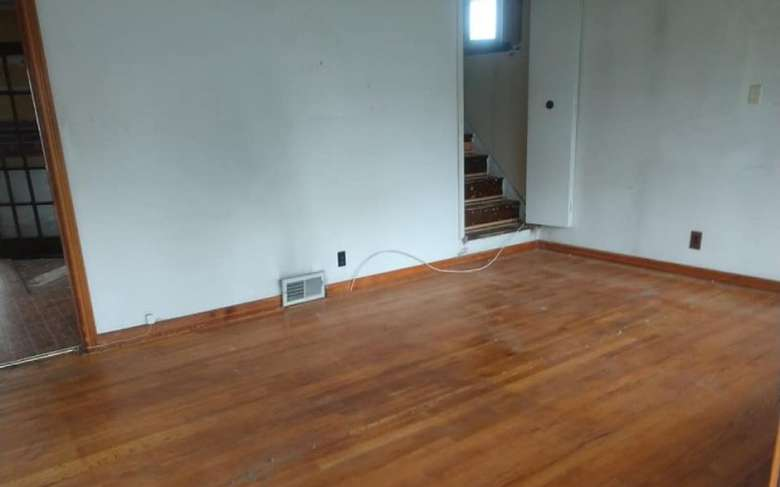 an empty living room with a wooden floor and a stairway