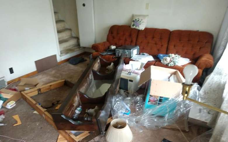 living room with a couch and piles of junk