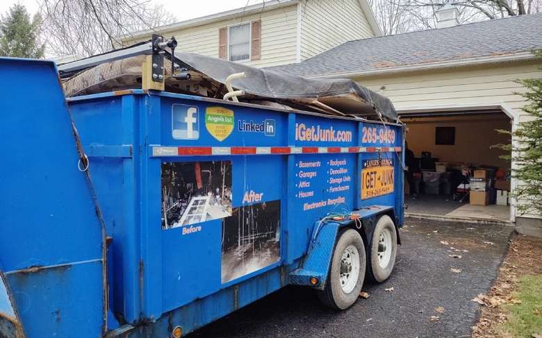 a large blue junk truck outside a house
