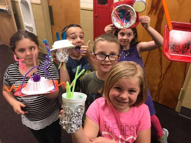 kids holding up crafts