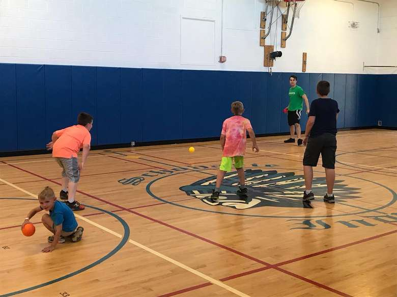 kids playing dodgeball in a gym