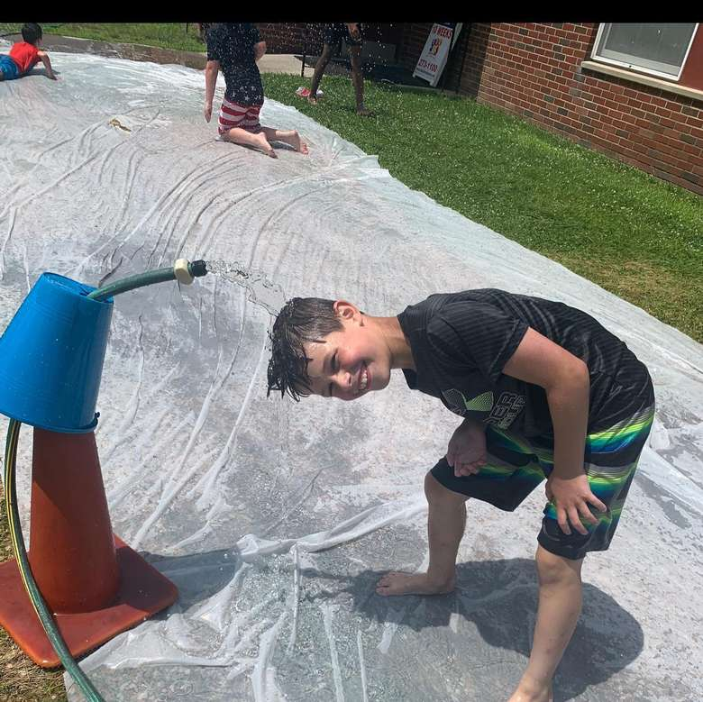 boy with head under sprinkler