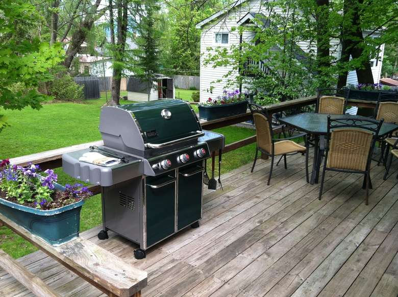 grill and table and chairs on a deck