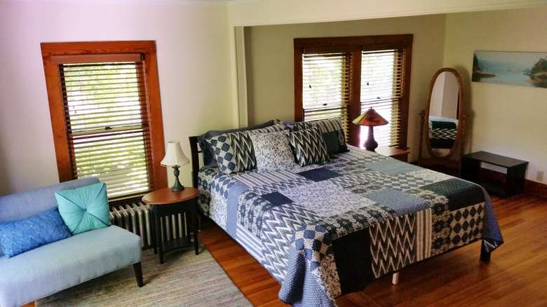 bedroom with bed that has pillows and blanket with blue and white design