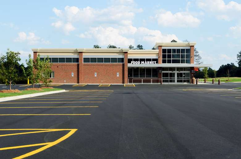 outside of a brick food market building with paved parking lot