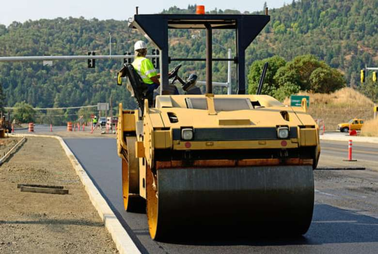 a paving construction vehicle and worker at the wheel