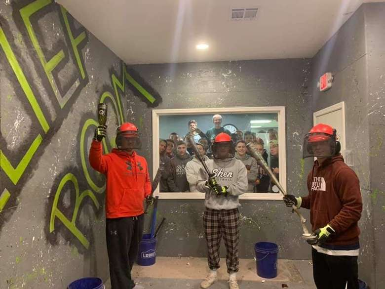 three people holding up tools in a rage room with a window showing other people