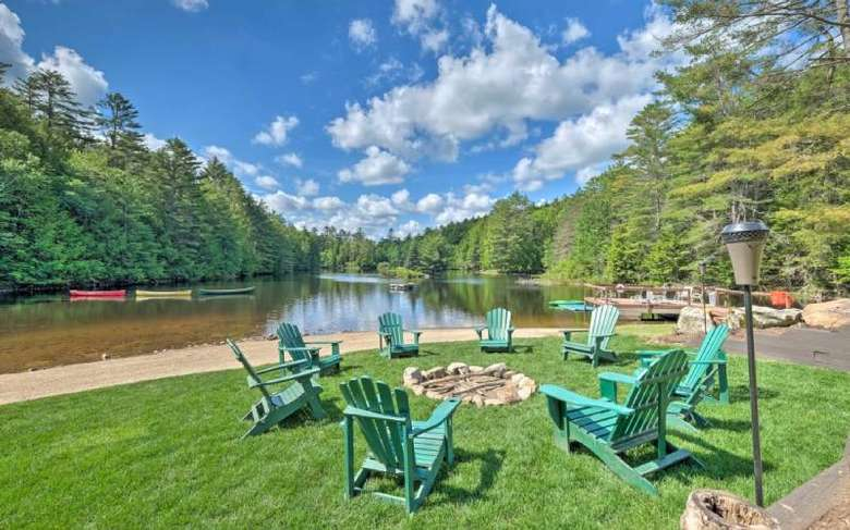 green chairs around fire pit by a lake