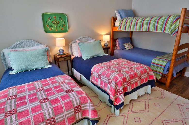 kids bedroom with two beds and bunk bed