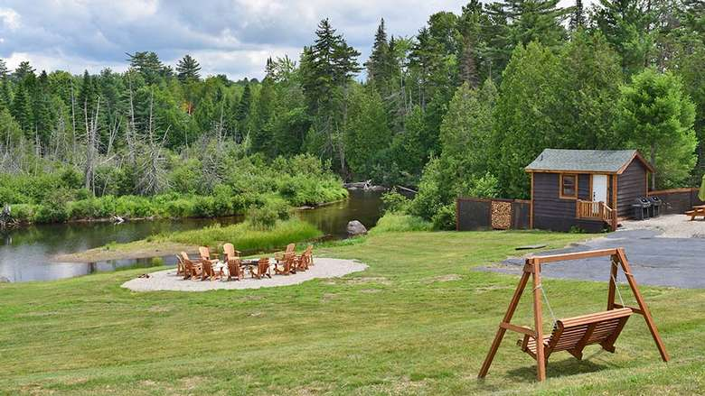 back lawn area with swinging chair and chairs around a fire pit