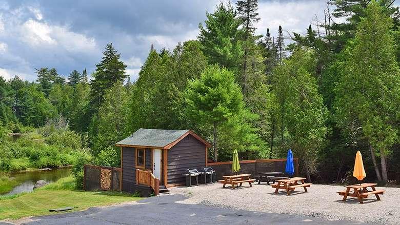 a dark wooden cabin near picnic tables
