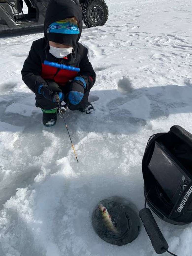 Boy ice fishing for perch on Lake George.
