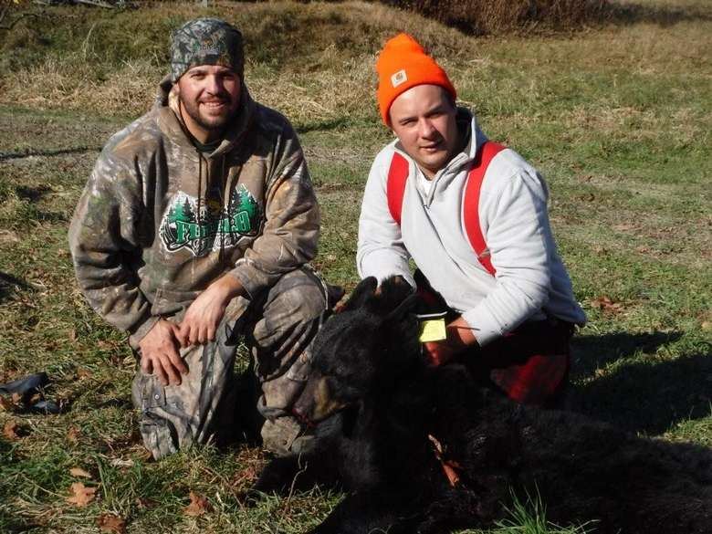 Two men with a black bear harvested on the ground.