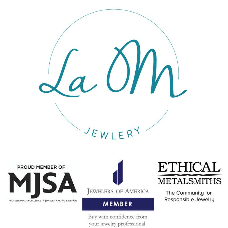 Logo Of La OM Jewelry, in cursive font, in a circle. Beneath the logo are logos of organizations La OM Jewelry belongs to. Jewelers of America, Manufacturing Jewelers Supply Association, and Ethical Metalsmiths.