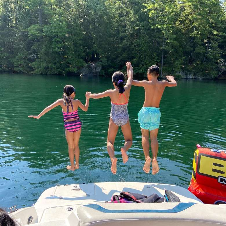 kids in mid-jump off boat