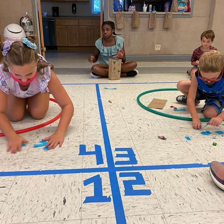 kids playing four square indoors
