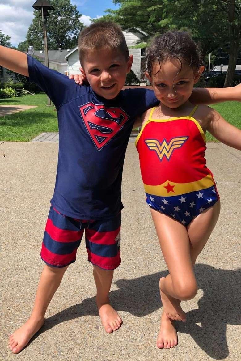 kids in super hero swim suits posing