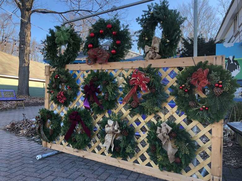 wreaths displayed on a wooden fence