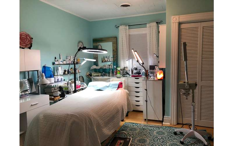 a treatment room with a bed, lights, and desks