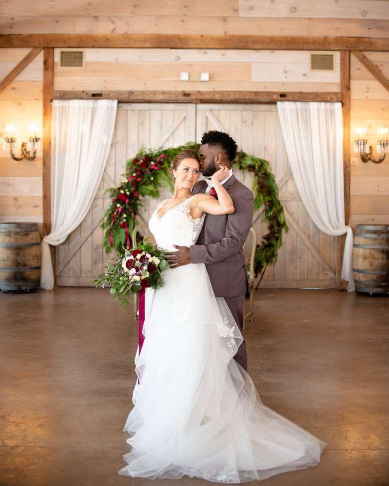 bride and groom standing on the open floor in a rustic room