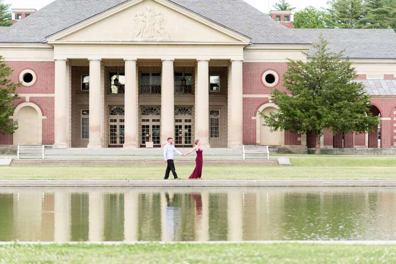 woman and man outside a brick building and pond