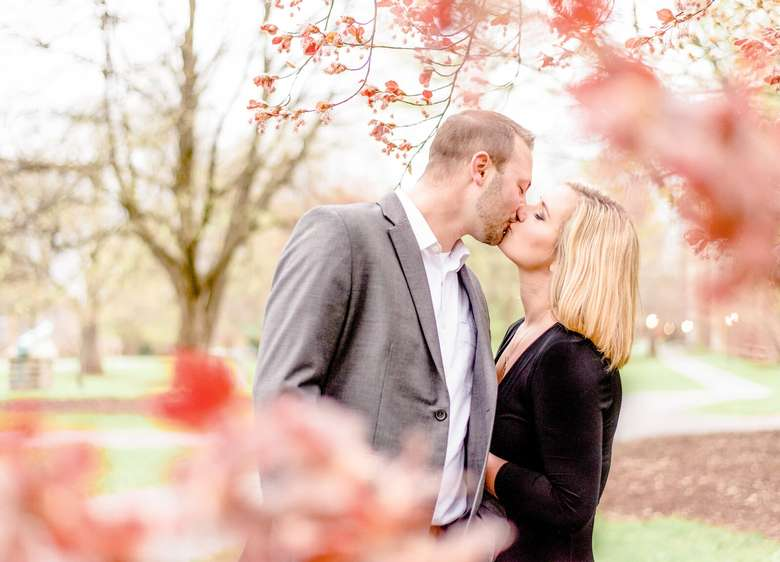 man and woman kissing outdoors near trees