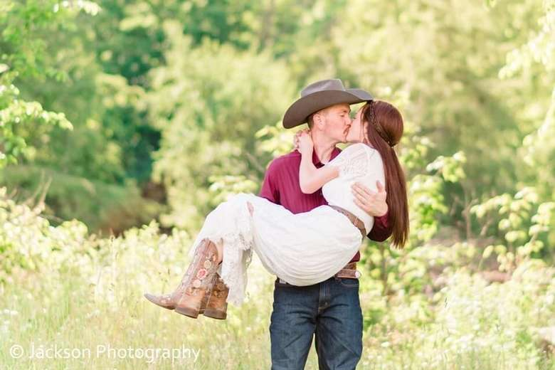 man wearing cowboy hat holding up and kissing a woman