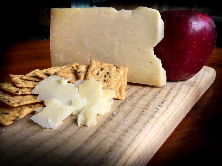 cheese, crackers, and apple on cheese board