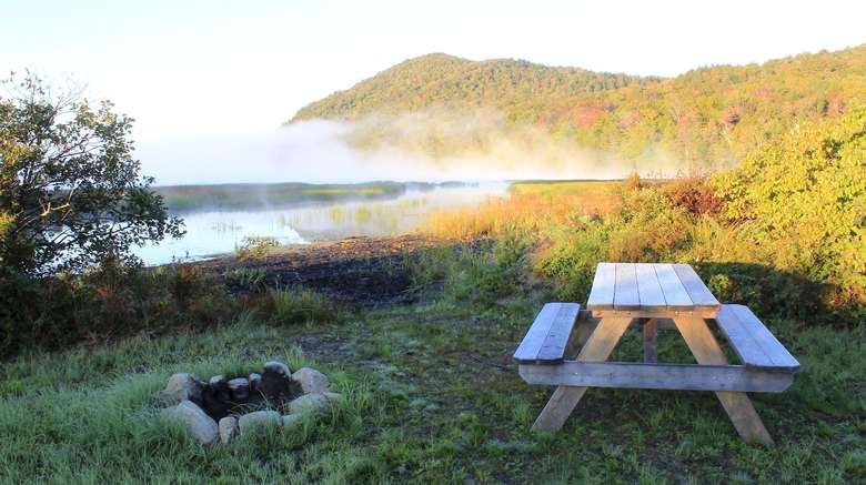 picnic table and fire pit by a lake