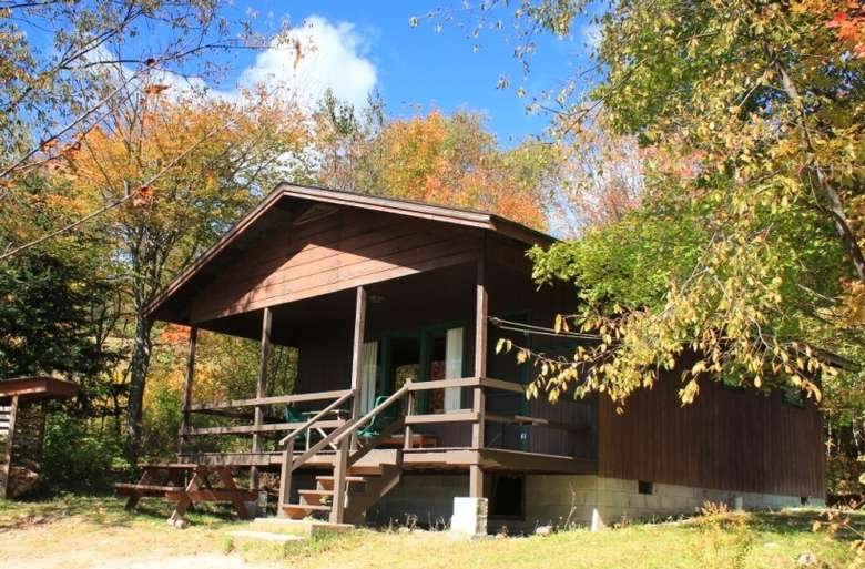 a cabin surrounded by trees with fall colors