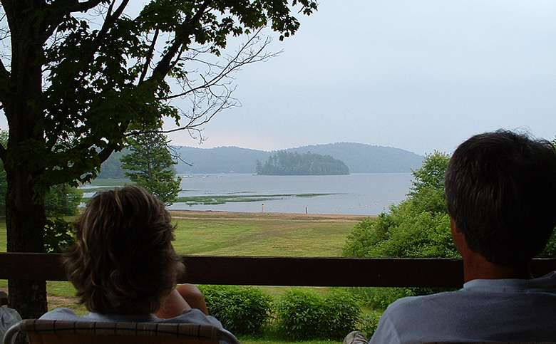 two people on a porch looking at a lake