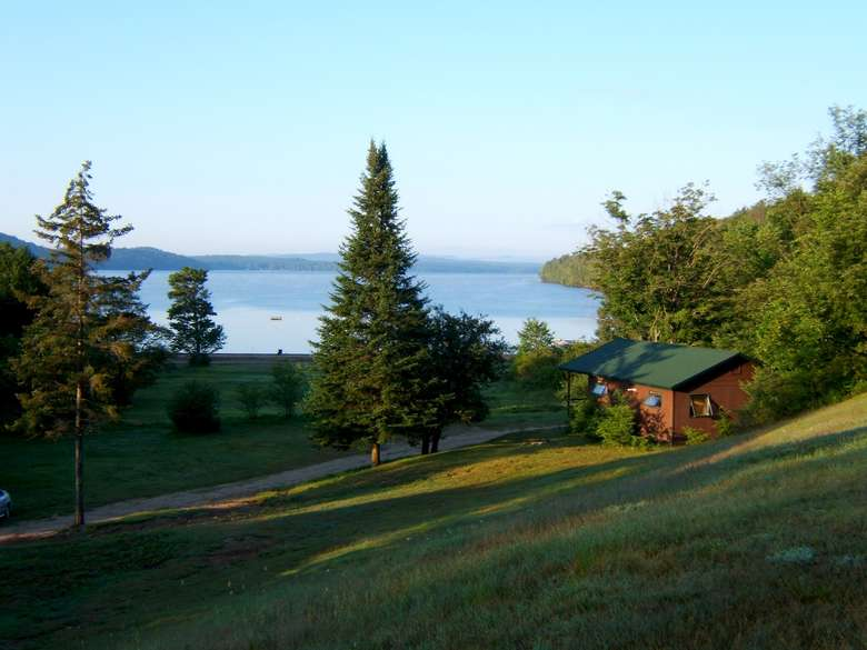 view of grassy lawn, a cabin, and a lake in the distance