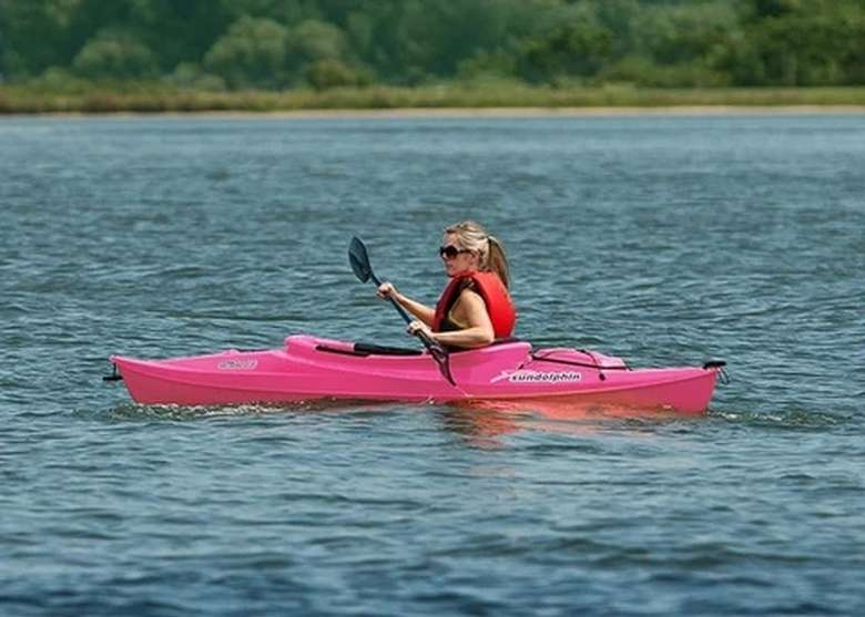 woman in a pink kayak on a lake