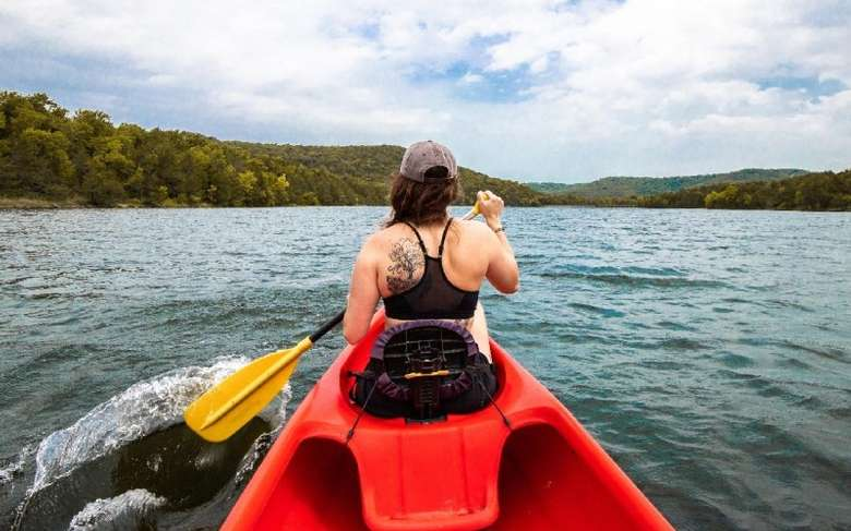 woman in a red kayak on a lake