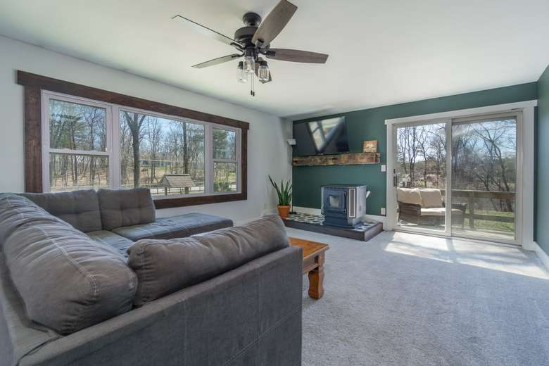 living room with couch, ceiling fan, windows, and a sliding glass door