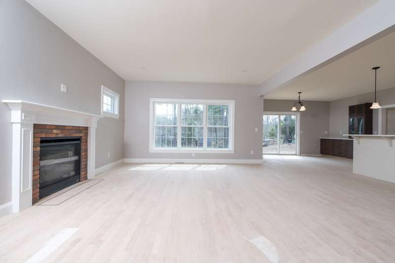 an empty living room with a fireplace on one wall