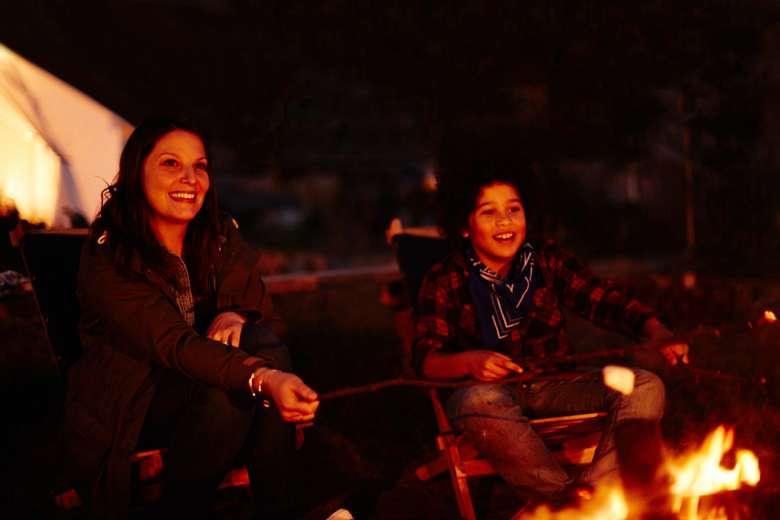 woman and teen roasting marshmallows at a campfire