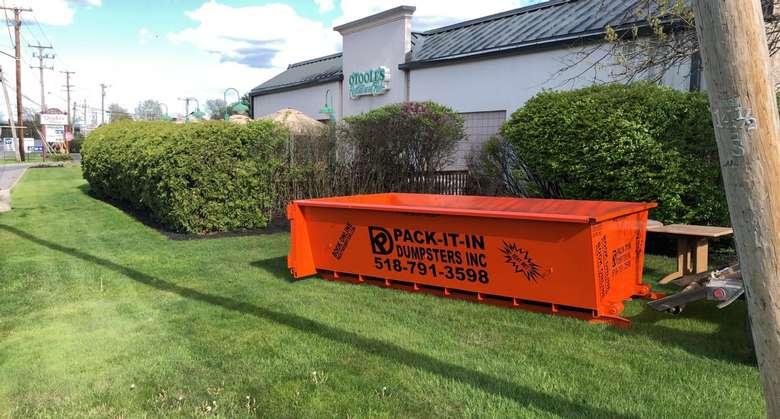 orange dumpster on lawn