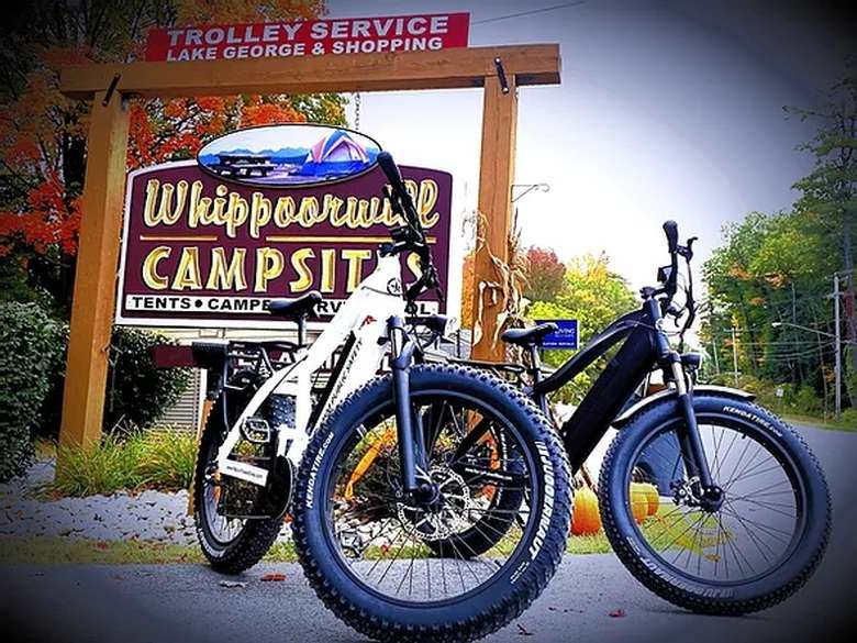 two electric bikes by a campsites sign