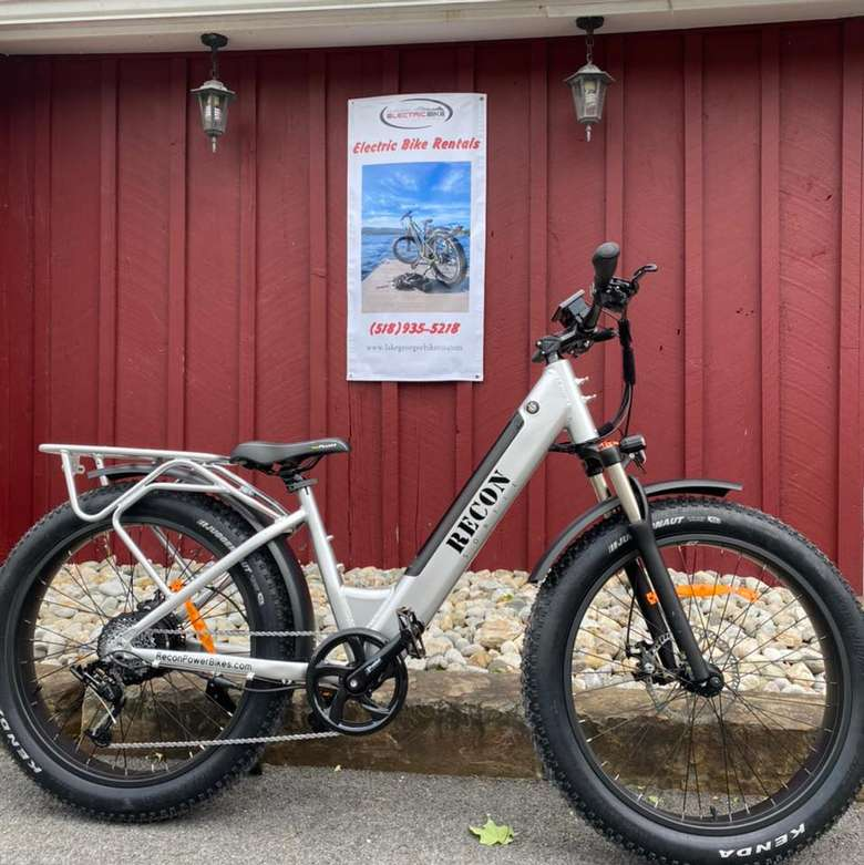 an electric bike in front of a red wall outdoors