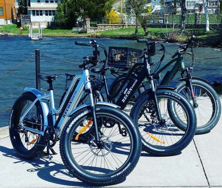three electric bikes by the water