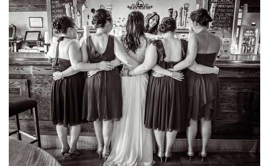 bridal party linking arms at a bar