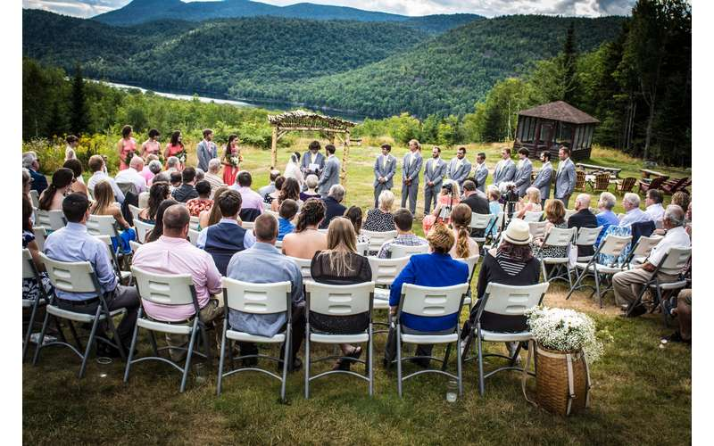 wedding guests seated for ceremony outdoors, mountains in background