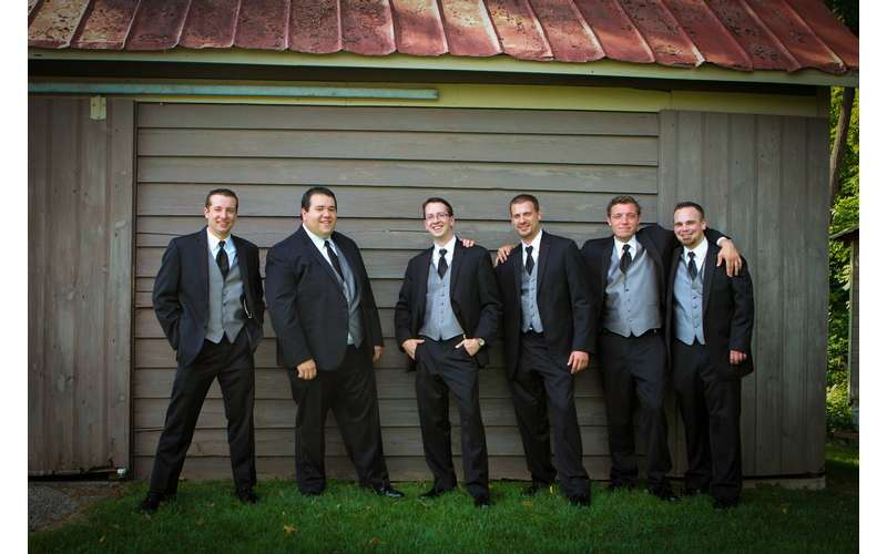 groom and groomsmen posing in front of a barn