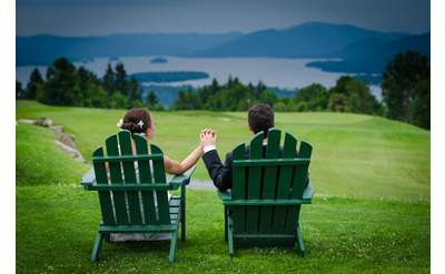 bride and groom in Adirondack chairs holding hands, looking out at mountains