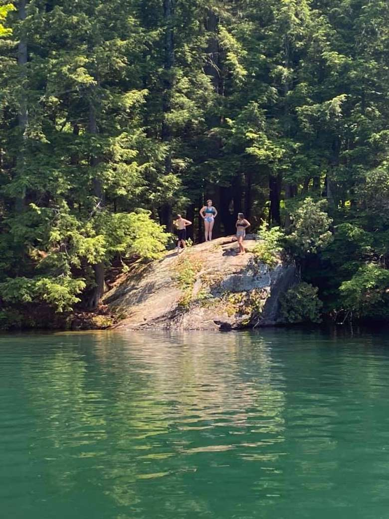 three people prepare to cliff jump into a lake