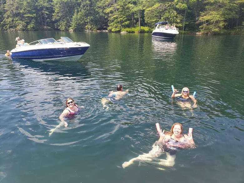 four people swimming in a lake